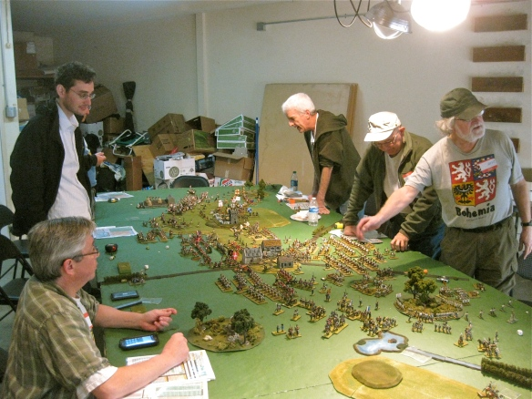 General view of the tabletop action. Rob, then Mark and hidden Dan line the French side of the table. Across from them is (l to r) Bob, Ty then Dave. Greg is off picture talking with Dave.