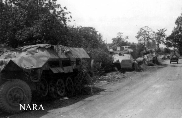 Roncey Pocket showing German halftrack abandoned or destroyed. Note the roadway was cleared by pushing the wrecks into the hedgerow lining the roadway.